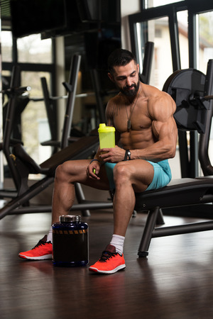 Muscular Man Resting After Exercise And Drinking From Shaker Stock Photo