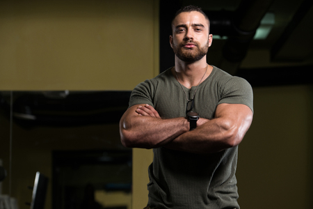Portrait Of A Young Physically Fit Man Showing His Well Trained Body In Green Shirt and Army Pants - Muscular Athletic Bodybuilder Fitness Model Posing After Exercises Stock Photo