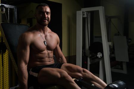 Man Doing Leg With Machine In Gym - Leg Exercises Stock Photo