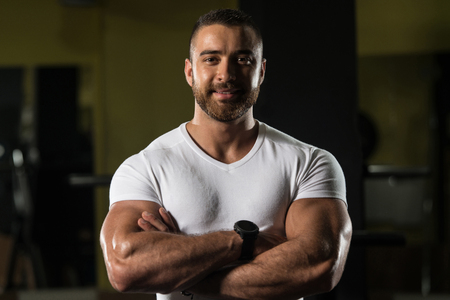 Handsome Young Man Standing Strong In White T-shirt And Flexing Muscles - Muscular Athletic Bodybuilder Fitness Model Posing After Exercises