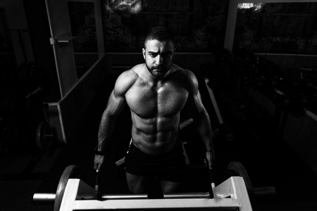 Model Doing Heavy Weight Exercise For Trapezius On Machine Stock Photo