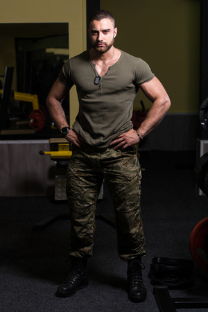 Handsome Man Standing Strong In Green T-shirt And Army Pants Flexing Muscles - Muscular Athletic Bodybuilder Fitness Model Posing After Exercises Banque d'images
