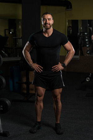 Handsome Young Man Standing Strong In Black T-Shirt And Flexing Muscles - Muscular Athletic Bodybuilder Fitness Model Posing After Exercises