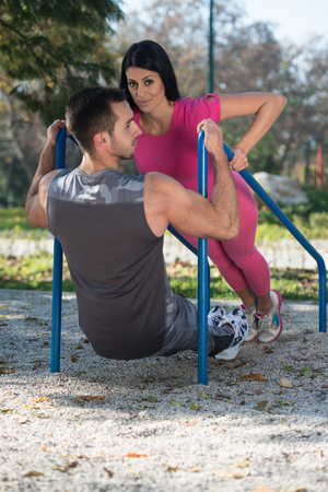 Attractive Couple Doing Crossfit Exercise With Dips Bar in City Park Area - Training and Exercising for Endurance - Healthy Lifestyle Concept Outdoor