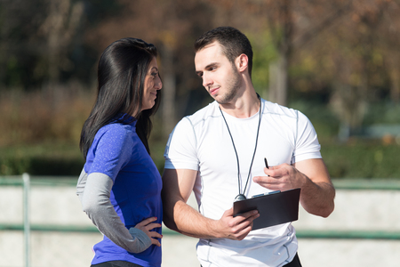 Personal Trainer Takes Notes While Young Woman Exercise in City Park Area - Training and Exercising for Endurance - Healthy Lifestyle Concept Outdoor Stock Photo