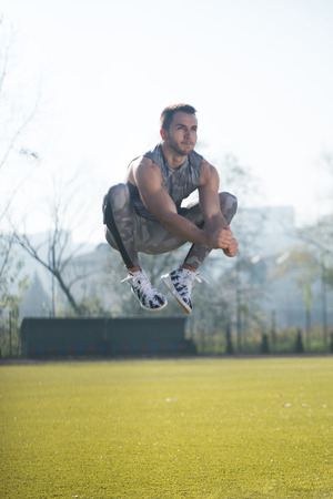 Attractive Man Doing Jumping in City Park Area - Training and Exercising for Endurance - Fitness Healthy Lifestyle Concept Outdoor Stock Photo