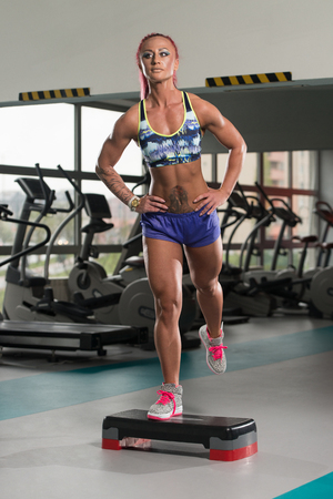 Young Woman Athlete Doing Exercise On Stepper As Part Of Bodybuilding Training