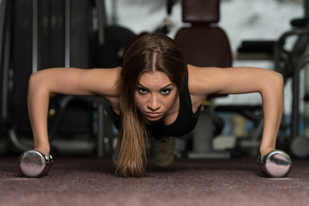 Young Adult Athlete Doing Push Ups With Dumbbells As Part Of Bodybuilding Training