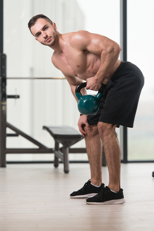 Man Exercising With Kettle Bell And Flexing Muscles - Muscular Athletic Bodybuilder Fitness Model Exercises Stock Photo