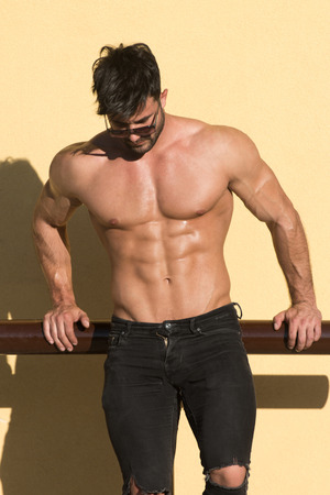 Portrait of a Young Physically Fit Man Showing His Well Trained Body While Wearing Black Jeans - Muscular Athletic Bodybuilder Fitness Model Posing After Exercises Outdoors - a Place for Your Text