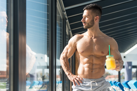Young Man Resting By Swimming Pool and Sun Loungers With Orange Juice