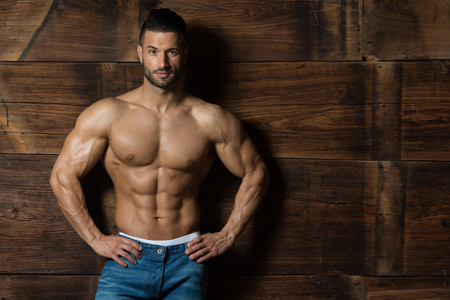 Portrait of a Young Physically Fit Man Showing His Well Trained Body While Wearing Blue Jeans - Muscular Athletic Bodybuilder Fitness Model Posing After Exercises on Wooden Wall - a Place for Your Text