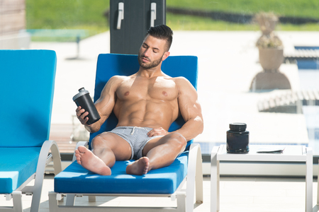 Young Man Resting On Sun Loungers By Swimming Pool With Supplements Pills And Dope or Shaker for Copy Space - a Place for Your Text Stock Photo