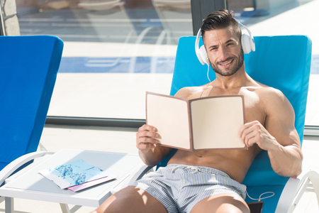 Young Man Resting On Sun Loungers By Swimming Pool and Listening Music On Headphones