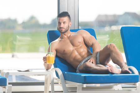 Young Man Resting On Sun Loungers By Swimming Pool With Orange Juice