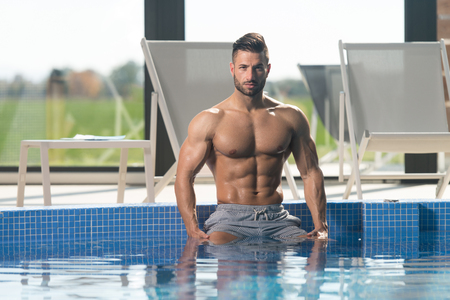 Young Healthy Good Looking Macho Man Model Athlete At Hotel Indoor Pool 写真素材 - 97514629