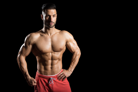 Young Bodybuilder Flexing Muscles - Isolate On Black Blackground - Copy Space Stock Photo