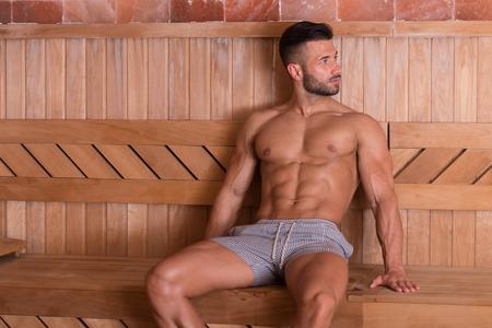 Happy Good Looking And Attractive Young Man With Muscular Body Relaxing In Hot Sauna Stock Photo