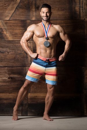 Bodybuilder Competitor Showing His Winning Medal Against a Wooden Wall and Flexing Muscles While Wearing Sports Shorts - Male Fitness Competitor Showing His Winning Medal a Place for Your Text