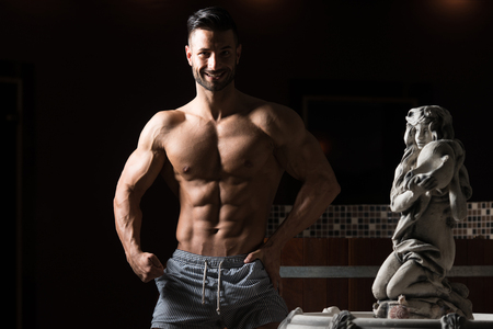 Healthy Young Man Standing Strong In Hot Sauna And Flexing Muscles - Muscular Athletic Bodybuilder Fitness Model Posing After Exercises