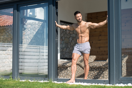 Serious Man Standing And Flexing Muscles At Sunny Day Stock Photo