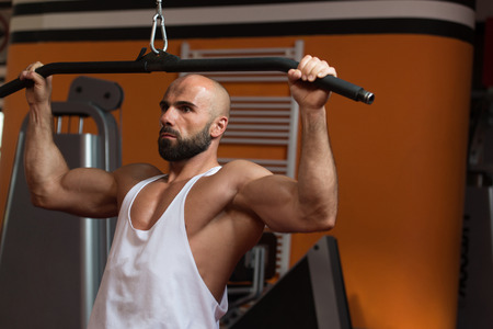 Handsome Bodybuilder Doing Heavy Weight Exercise For Back On Machine In Gym