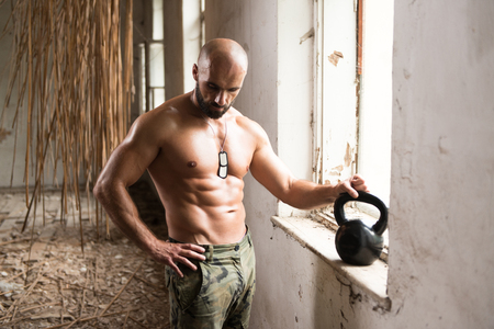 Man Exercising With Kettle Bell And Flexing Muscles - Muscular Athletic Bodybuilder Fitness Model Exercises In Ruins