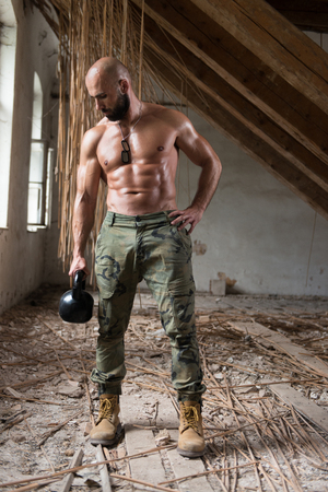Man Working Out With Kettle Bell In Shelter - Bodybuilder Doing Heavy Weight Exercise With Kettle-bell Stock Photo