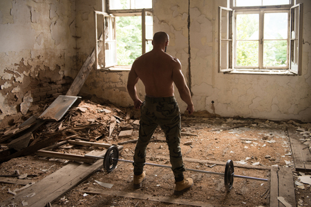 Portrait of a Physically Fit Man Showing His Well Trained Body - Muscular Athletic Bodybuilder Fitness Man Posing After Exercises Inside Shelter
