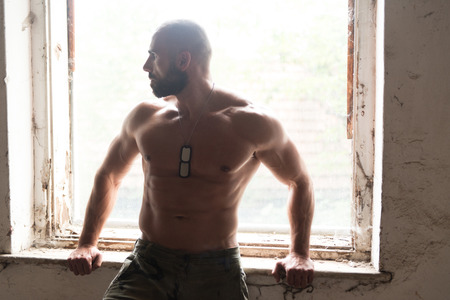 Portrait of a Physically Fit Man Showing His Well Trained Body - Muscular Athletic Bodybuilder Fitness Man Posing After Exercises Inside Refuge