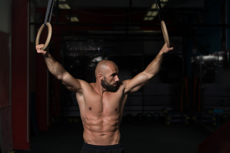 Adult Man Exercising While Holding Large Gymnastic Rings At The Gym Stock Photo