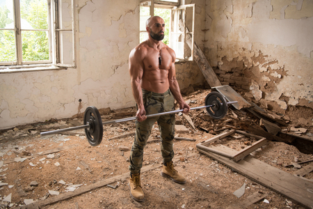 Handsome Muscular Fitness Man In Army Pants Doing Heavy Weight Exercise For Biceps With Barbell Inside Shelter