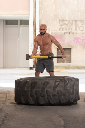 Athletic Man Hits Tire - Workout At Gym With Hammer And Tractor Tire Stock Photo