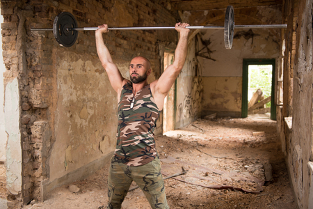 Muscular Man Doing Heavy Weight Exercise For Shoulders With Barbell In Refuge Stock Photo