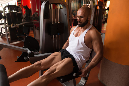 Leg Exercises -  Man Doing Leg With Machine In Gym Stock Photo