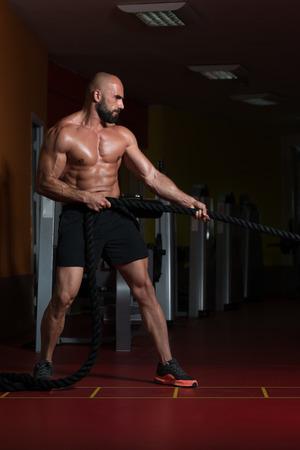 Man Battling Ropes At Gym Workout Exercise