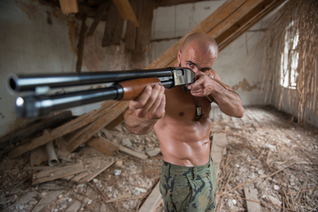 Action Hero Muscled Man Holding Machine Gun - Standing In Abandoned Building Wearing Army Pants