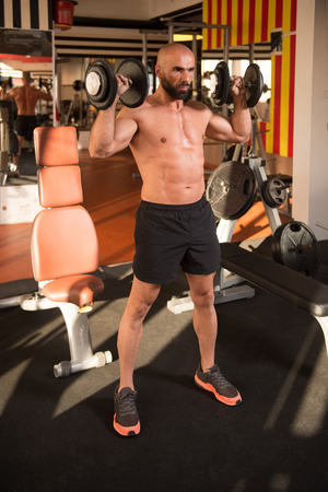 Strong Man In The Gym And Exercising Shoulders With Dumbbells - Muscular Athletic Bodybuilder Fitness Model Exercise Shoulder