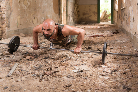 Athlete In Army Pants Doing Heavy Weight Exercise Push-Up As Part Of Bodybuilding Training Stock Photo