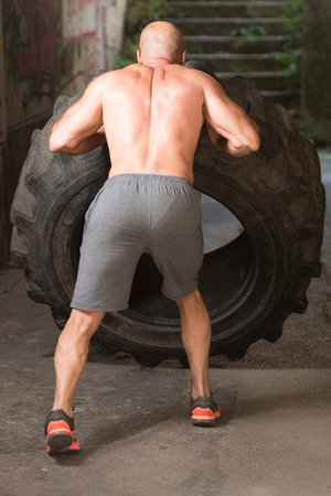 Young Muscular Man With Truck Tire Doing Crossfit Style Workout Turning Tire Over