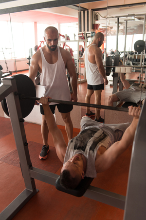 Personal Trainer Showing Young Man How To Train Chest Exercise With Barbell In A Health And Fitness Concept