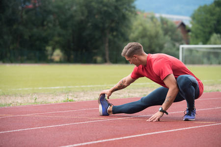 Young Athlete Man Relax and Strech Ready for Run at Athletics Race Track on Stadium Stock Photo