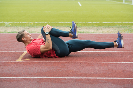 Il giovane atleta Man Relax e Strech pronto per l'esecuzione alla pista di atletica sullo stadio Archivio Fotografico