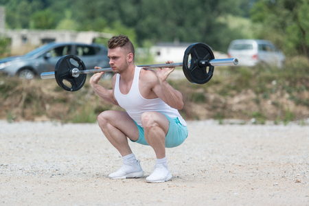 Man Working Out Legs In Outdoors With Barbell