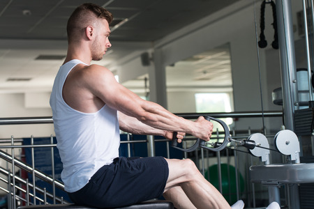 Handsome Muscular Fitness Bodybuilder Doing Heavy Weight Exercise For Back On Machine With Cable In The Gym Stock Photo