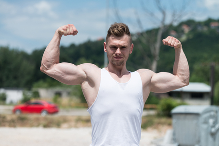 Healthy Young Man Standing Strong Outdoors  And Flexing Muscles - Muscular Athletic Bodybuilder Fitness Model Posing After Exercises Stock Photo