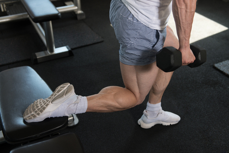 Athlete Working Out Hamstrings In A Gym With Dumbbells