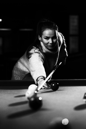 Young Woman Lining To Hit Ball On Pool Table Фото со стока