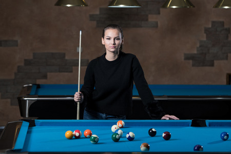 Portrait Of A Young Girl Playing Billiards Фото со стока