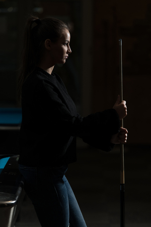 Young Woman Looking Confused At Billiard Table - She Is Losing Фото со стока